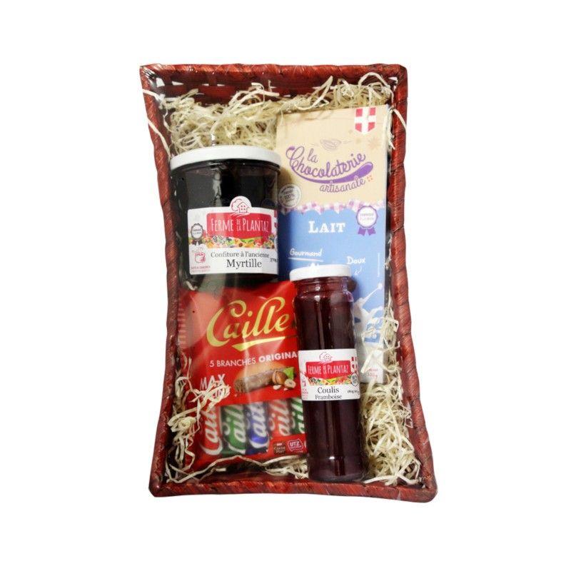 Panier festif avec tablette de chocolat au lait, branches au chocolat au lait, coulis à la framboise et confiture à la myrtille